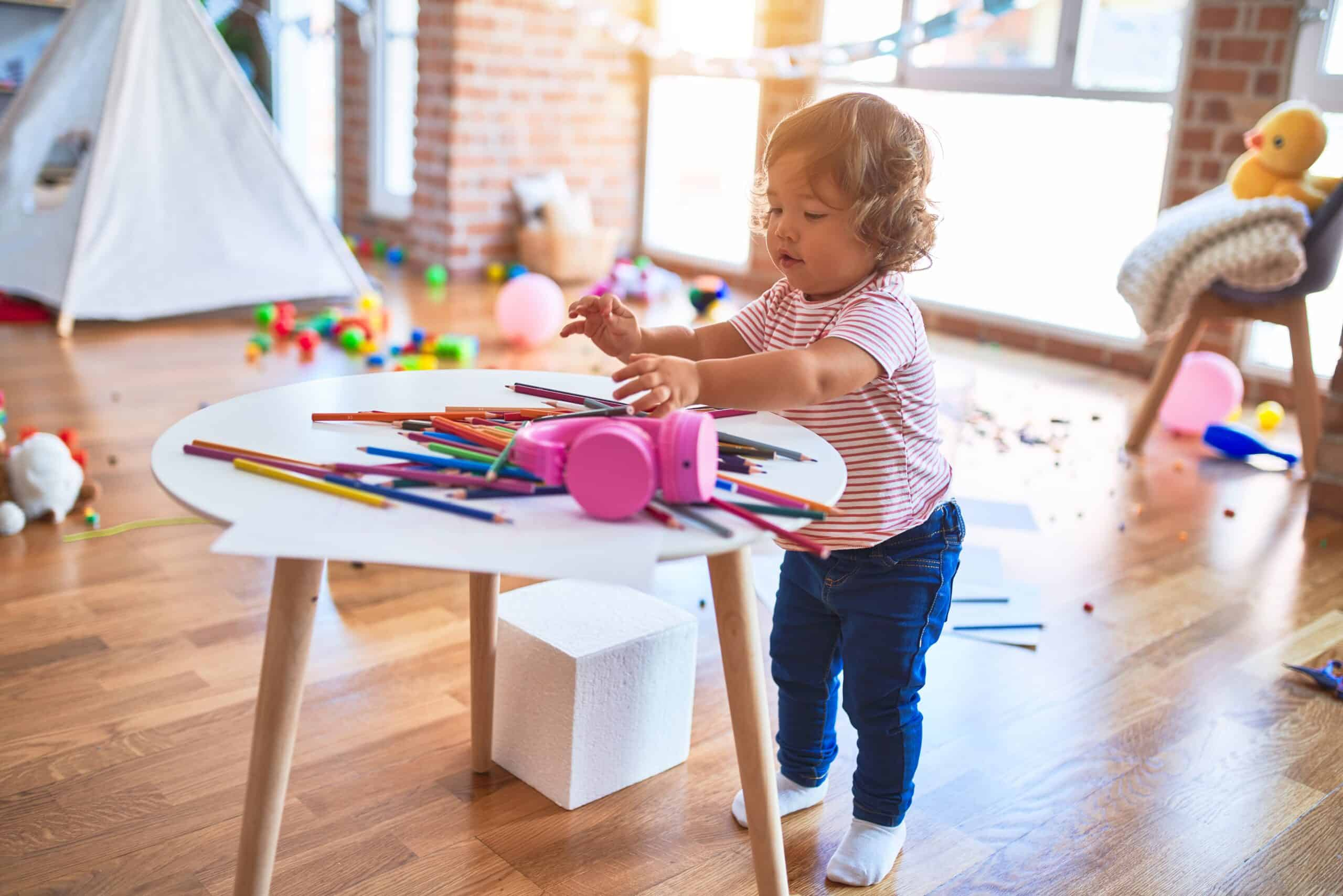 Image of a child playing with colored pencils showing play leads to discovery of the world.