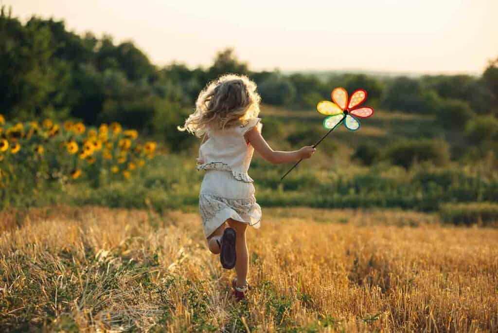 Image of strong-willed girl running through a field with a pinwheel.