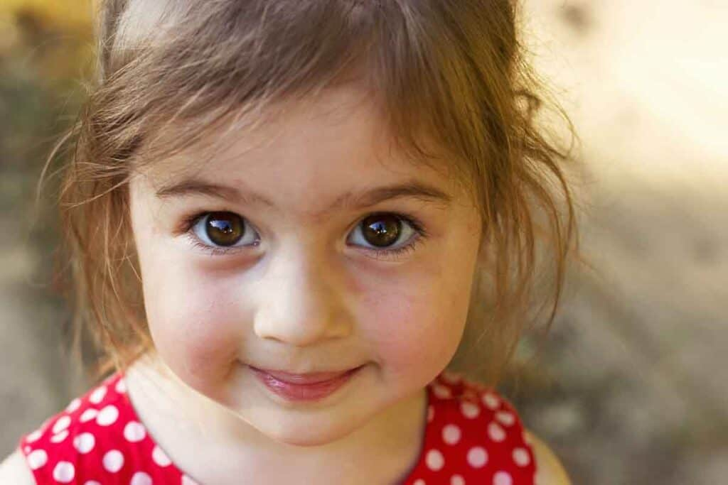 Image of a girl looking defiant, but happy and cute.